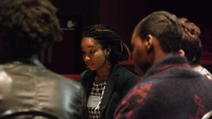 A close-up view into a breakout conversation. A young woman listens intently to someone on the far side of the group.