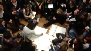 a person wearing white writes notes on flipchart paper in the misddle of a very big group all wearing dark colours.