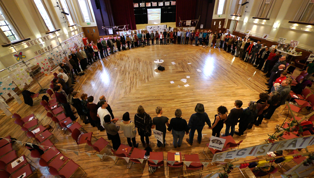 A circle of participants seen from above, all holding hands.